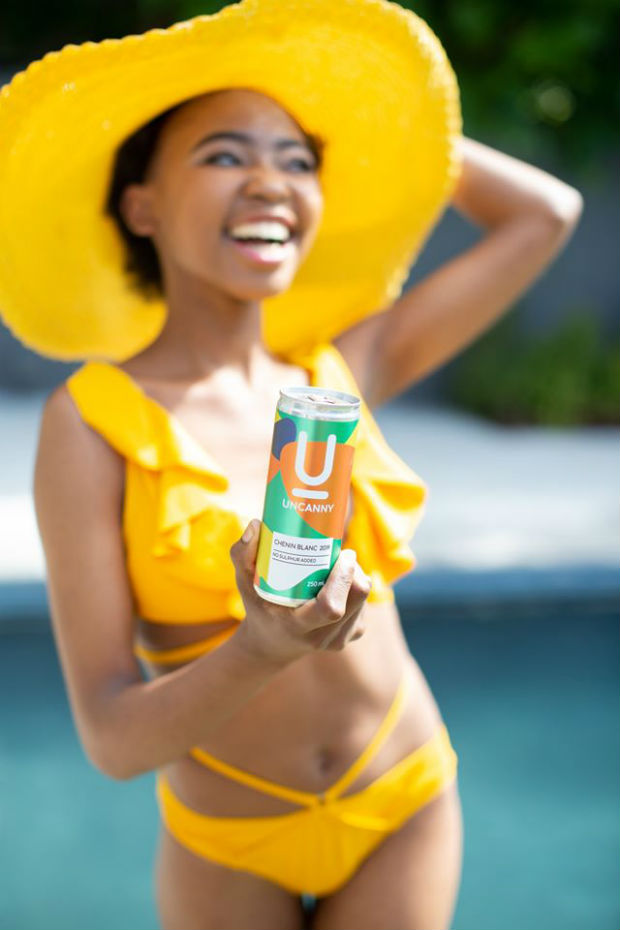 woman holding a can of wine near the pool